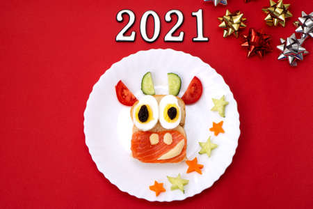 Funny sandwich with edible symbol of 2021 bull cow made from toast bread, red fish, cheese, raisins, eggs and vegetables. Breakfast idea for kids. christmas food top view. food art
