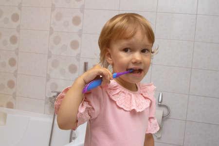 Little girl in pink pyjamas in bathroom brushing her teeth Imagens