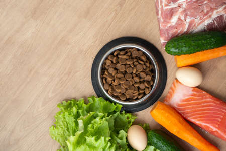 Dry pet dog food with natural ingredients. Raw meat, fish, vegetables, eggs and salad near bowl with dry pet feed on wooden background. concept of correct balanced nutrition for pet, copy space