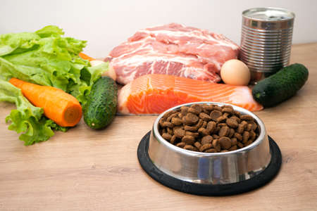 Dry pet dog food with natural ingredients. Raw meat, fish, vegetables, eggs and salad near bowl with dry pet feed. concept of a correct balanced and healthy nutrition for pet, close up