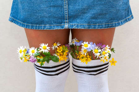 female legs with fresh flowers in stockings. A young hipster girl with flowers from white stockings and jeans skirt