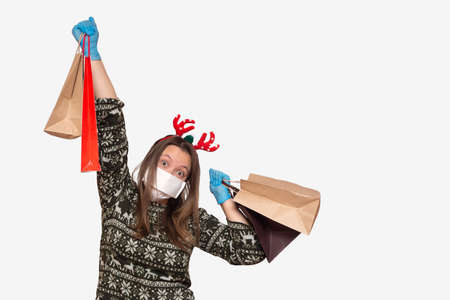 young European woman in a white medical mask and Christmas red hat with gift packages in hands. Christmas Shopping girl, quarantine coronavirus on xmas