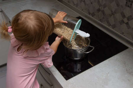 preparation of a family breakfast. kid girl help cook porridge in morning. little girl pours oat flakes into a saucepan.