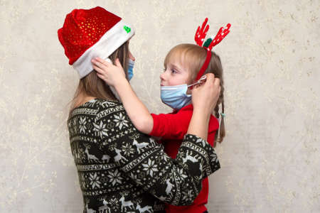 Family, mother and daughter in protective masks in quarantine at christmas holiday in santa klaus hat and deep antlers. Normal life with coronavirus. COVID-19 lifestyle. Quarantine virus protection.
