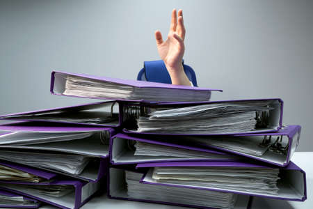 raised hands of a person who sinks behind stacks of ring binders on an office desk. concept of excessive demands and increasing work in business. selected focus