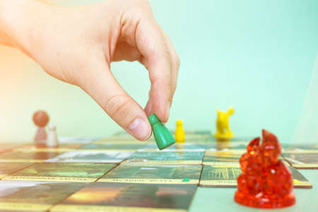 hand with chip under the playfield. Forbidden Island game cards and chips on table close up. Board game and leisure concept. Minsk, Belarus - July 10, 2021.