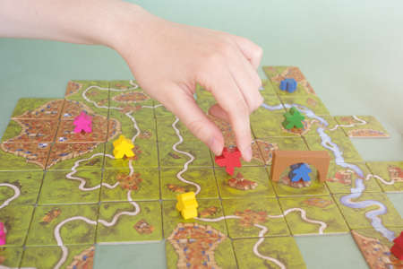 hand with chip under the playing field. Carcassonne game cards and chips on table close up. Board game and leisure concept
