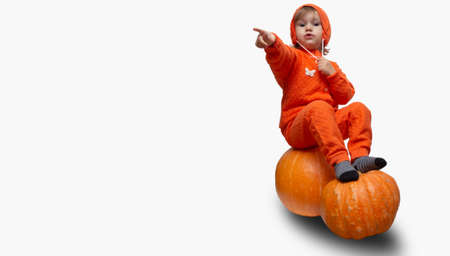 Kid girl in an orange suit sits on pumpkins and points a finger copy space. place for text Halloween