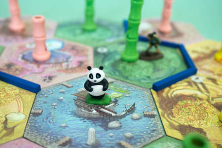 The tiles and meeples of tabletop board game Takenoko. Popular family hobby strategy board game. Minsk, Belarus - July 10, 2021