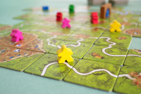 The tiles and meeples of tabletop boardgame Carcassonne with a roads and castles and river. Popular family hobby board game. Minsk, Belarus - July 10, 2021