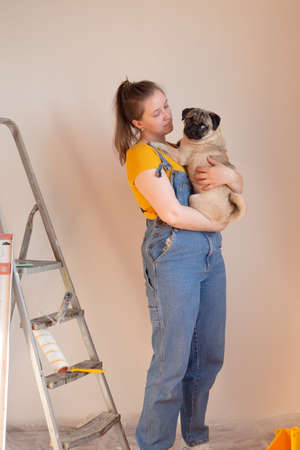 Happy woman makes repairs in her apartment with her funny pug dog. happiness in anticipation of a new home and moving. independent single life with a pet