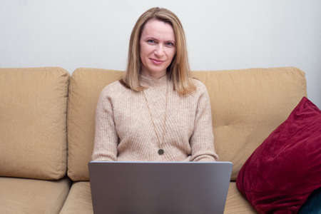 Woman sitting on cozy sofa and works from home or a student is studying from home or a freelancer. uses a laptop for remote meeting with friends and colleague