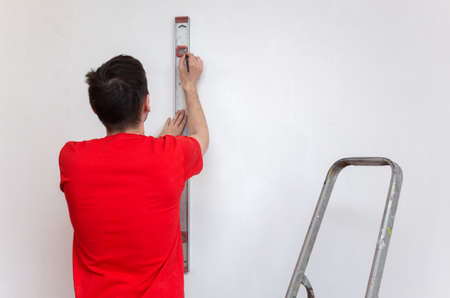Man repair worker checking level of the wall with the bubble level tool. Renovation apartment concept.