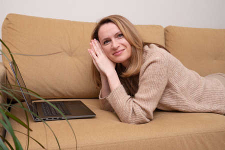 Woman lying on a sofa at home and working on a laptop computer. Cozy remote work. online consultation and psychotherapy session. looking at the camera