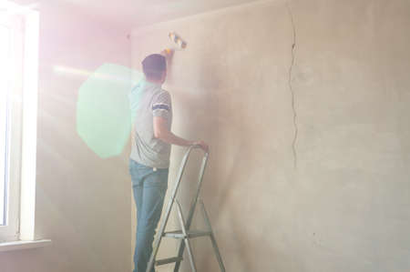 Man priming the wall with a roller. Repair of the interior with copy space. Young male decorator painting a wall in the empty room. Concept renovation do it yourself Foto de archivo