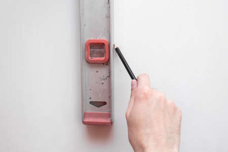 Man repair worker checking level of the wall with the bubble level tool. Renovation apartment concept. close up