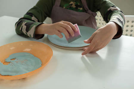 child painting with sponge on clay pottery plate in ceramic workshop studio. Development of art and painting in children. Close up