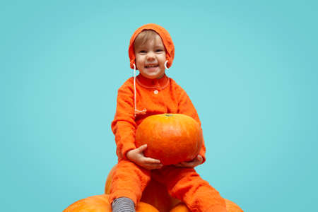 Kid girl in an orange suit sits on a big Halloween pumpkins and holding little pumpkin with copy space. place for text