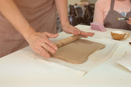 Female ceramist rolls clay using wooden rolling pin in ceramic studio. Close-up hands. Creating pottery.