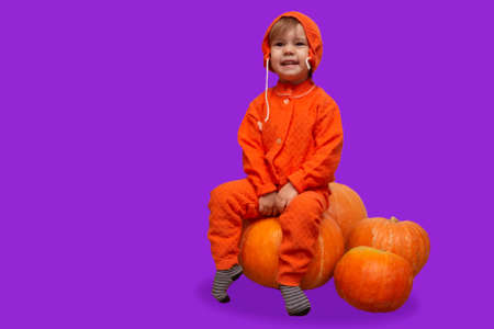 Kid girl in an orange suit sits on a big Halloween pumpkins with copy space. place for text