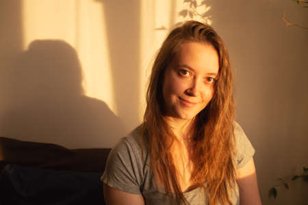 Young woman looking at camera in warm rays of sunset. Warm calm portrait of girl indoor. light and shadow on the face