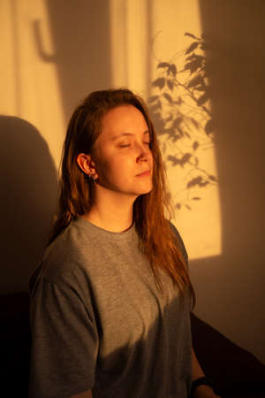 Young woman close eyes and relaxation in warm rays of sunset. Warm calm portrait of girl indoor Foto de archivo