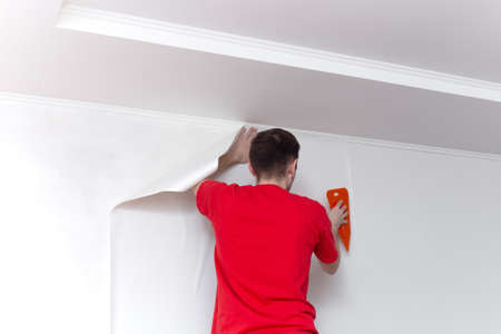 Young professional repairman glueing wallpapers on concrete wall. Repair apartment. Home renovation concept