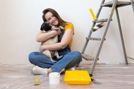 woman hugs pet dog in her new house during renovation, construction tools and ladder on the background. Independent single female life with pet