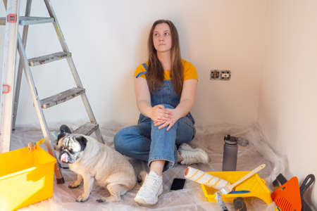 Independent young woman with pug dog planning renovation apartment sitting on floor with construction tool. diy repair owner hands with pet
