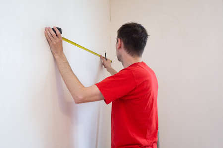 Man repair measures the white wall of the with a tape measure and before wallpapering. renovation apartment.