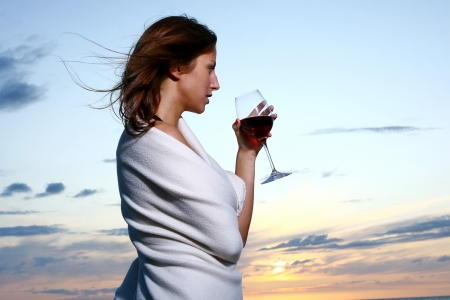 lit image: beautiful young woman drinking wine Stock Photo