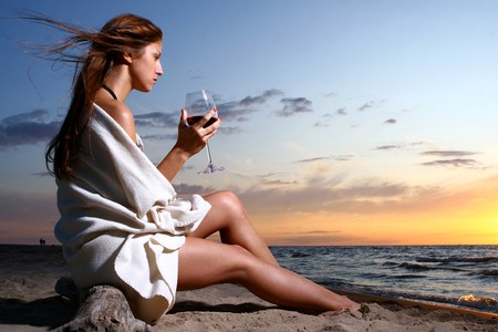 a beautyful  young woman drinking wine on the beach photo