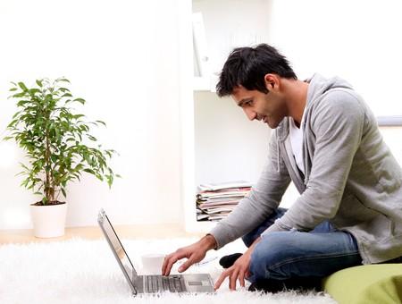 business man laptop: joven y noticias en el hogar Foto de archivo