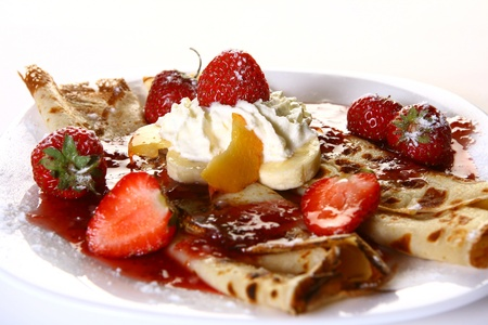 a dessert plate witn pancakes and strawberry photo