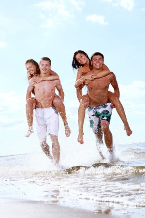 guy on beach: happy teenagers playing in the sea