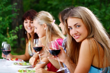 group of young and beautiful womens drinking wine in the park photo