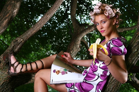 a beautiful young woman eating banan photo