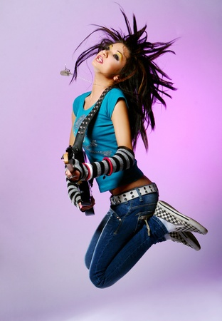 young beautiful girl jump with guitar photo