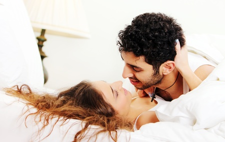 honeymoon couple: Young and beautiful couple in bed Stock Photo