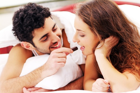 Young and beautiful couple having breakfast in bed photo