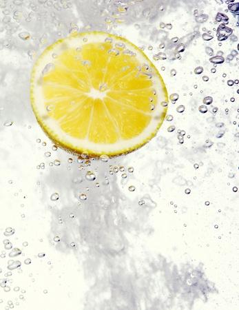 Fresh Lemon dropped into water photo