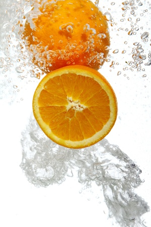 Fresh oranges dropped into water Stock Photo - 8599679