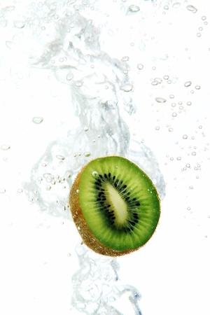 Fresh kiwi dropped into water photo