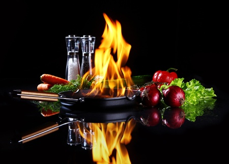 fryingpan: Frying pan with burning fire inside and fresh vegetables around