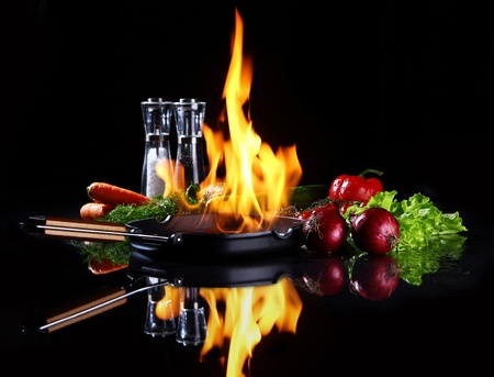 Frying pan with burning fire inside and fresh vegetables around photo