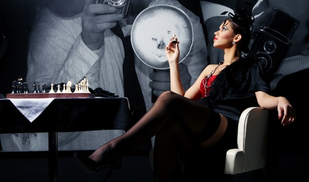 beside: Young and sexy vintage woman posing beside chess table Stock Photo
