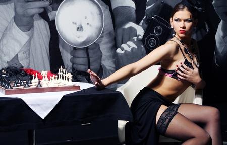 deseo sexual: Young y sexy mujer vintage posando al lado de la tabla de ajedrez