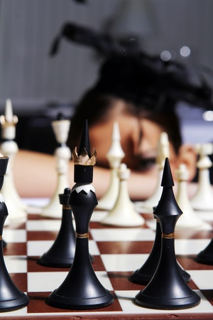 Young and sexy topless woman behind chess figures photo