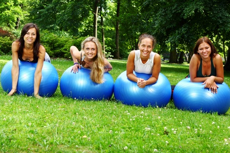 Young and attractive womans doing fitness exercises in park photo
