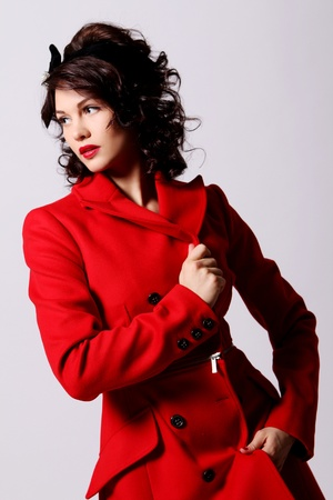 Beautiful young woman in red coat posing on white background photo